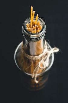 Dettaglio degli spaghetti di pasta in una bottiglia vuota di vetro olio d'oliva su sfondo nero
