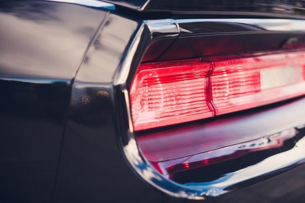 Dettaglio del faro posteriore nero metallizzato rosso a forma di occhio, con riflesso del sole nella pupilla.
