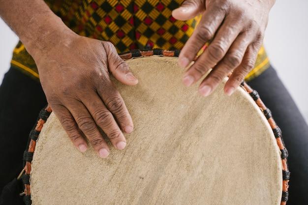 Dettaglio del musicista afroamericano dell'uomo che suona i tamburi tradizionali a casa. concetto di classe di musica online. strumenti musicali per l'apprendimento del tempo libero. stile ritmico e blues. tradizioni etniche multiculturali.