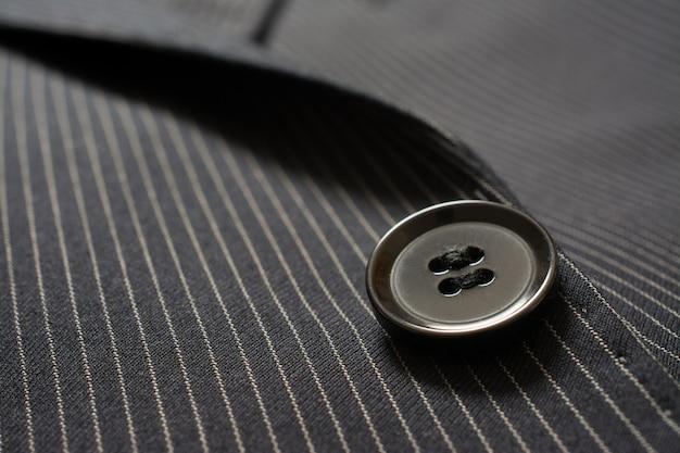 Dettaglio del primo piano del pulsante vestito sul panno spogliato perno