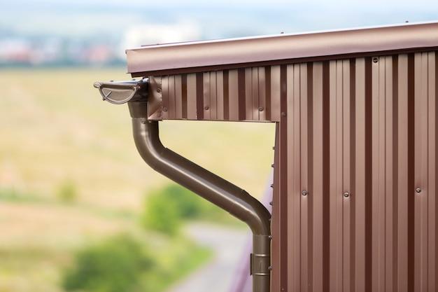 Dettaglio del primo piano dell'angolo della casa del cottage con il raccordo delle plance del metallo e tetto con il sistema della pioggia della grondaia.