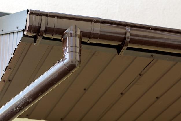 Dettaglio del primo piano dell'angolo della casa del cottage con il raccordo marrone delle plance del metallo e tetto con il sistema della pioggia della grondaia d'acciaio. tetto, costruzione, installazione dei tubi di drenaggio e concetto del collegamento.