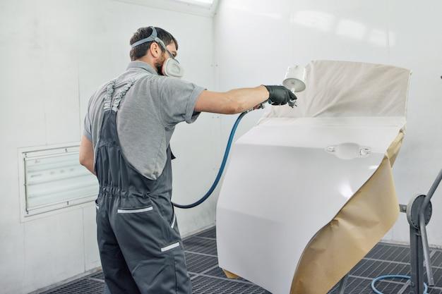 Dettaglio del primo piano della macchina. la vernice viene applicata sulla superficie della macchina