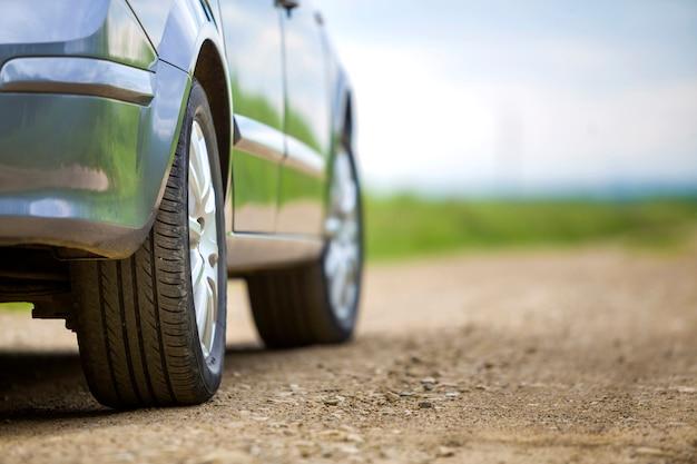 Dettaglio del primo piano della parte dell'automobile, ruote con disco in alluminio e protezione della gomma di gomma nera su sfondo chiaro all'aperto. concetto di viaggio e veicoli.
