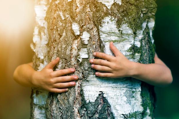 Dettaglio del primo piano di grande tronco di albero forte crescente isolato abbracciato da dietro dalle piccole mani bianche del bambino sull'amore vago alla natura, alla cura per il futuro e al concetto di protezione dell'ambiente.