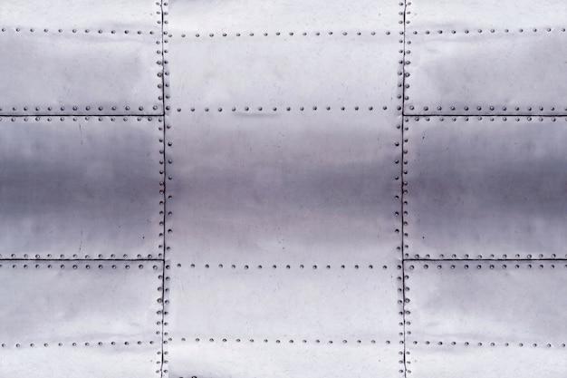 Dettaglio del vecchio pezzo di lerciume di piastra metallica con bulloni, sfondo di superficie in alluminio