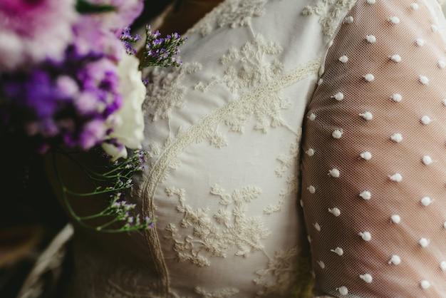 Dettaglio dell'abito da sposa e del suo bouquet.