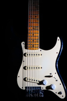 Dettaglio della chitarra elettrica su uno sfondo nero tra luce o ombre