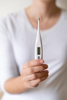 Dettaglio della donna in buona salute che misura con una febbre alta del termometro digitale. mantenere il controllo dei livelli di rischio di alta temperatura nel nostro corpo durante la crisi virale pandemica covid 19. infermiera irriconoscibile.