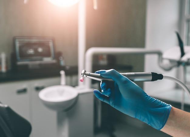 Dettaglio della mano che tiene gli strumenti dentali in clinica dentale. concetto del dentista.