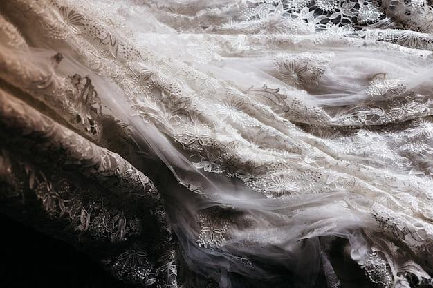 Dettaglio della trama di un abito da sposa bianco.