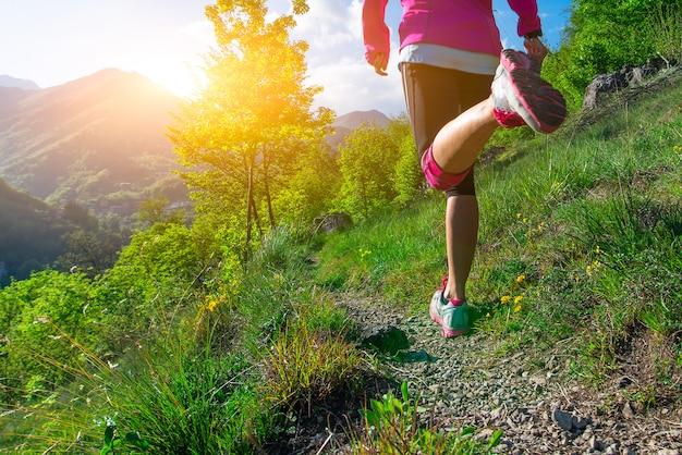 Dettaglio delle gambe di una ragazza che corre su un sentiero di montagna