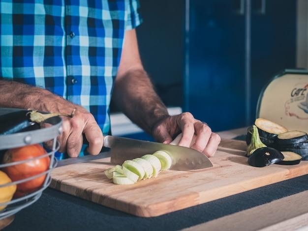 Dettaglio delle mani che tagliano porro organico sul bordo di legno