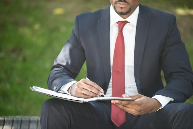 Dettaglio delle note di scrittura di un uomo d'affari mentre sedendosi su un banco