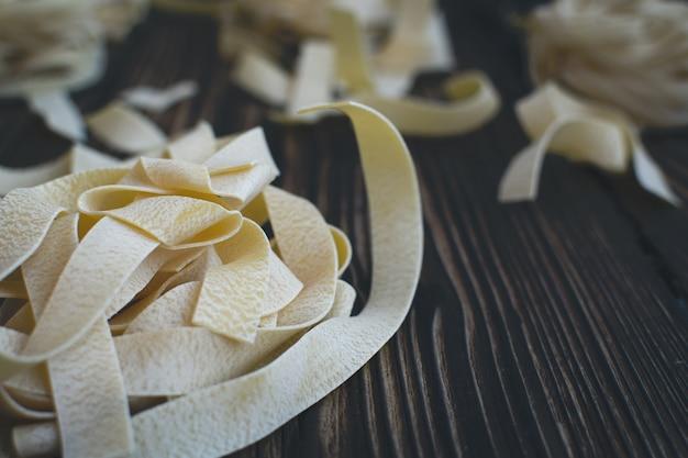 Dettaglio delle tagliatelle della pasta su un fondo di legno