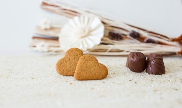 Dettaglio di biscotti e cioccolatini a forma di cuore con fiori carta con spazio per scrivere