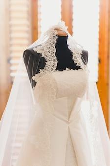 Dettaglio di un abito da sposa bianco appeso.