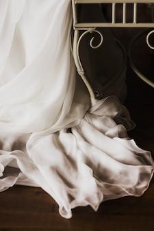 Dettaglio di un abito da sposa bianco ed elegante.
