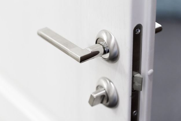 Dettaglio di una manopola metallica sulla porta bianca orizzontale