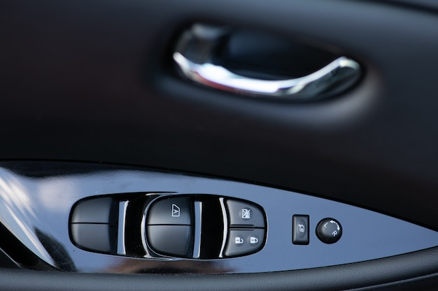 Dettaglio sui pulsanti che controllano i finestrini di un'auto. dettagli interni auto della maniglia della porta con comandi dei finestrini e regolazione degli specchi elettrici. pannello comandi finestrino e specchio sulla portiera del conducente