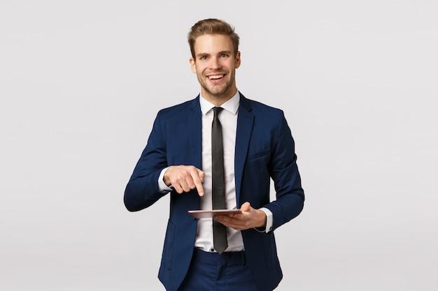 Devi vedere questo. imprenditore maschio elegante allegro in abito classico, cravatta, tenendo la tavoletta digitale e puntando lo schermo del gadget per mostrare al partner commerciale notizie fantastiche scritte sulla rivista online
