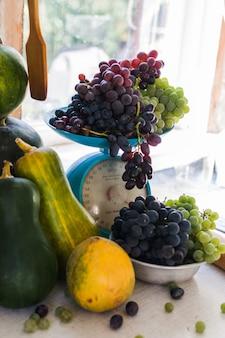 Di autunno vita ancora con zucche, meloni, anguria, uva su una scala e in una ciotola di metallo su un tavolo di legno bianco. concetto di vendemmia autunnale.