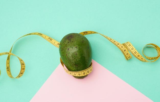 Di avocado verde e un nastro giallo di misurazione contorto su un fondo rosa verde