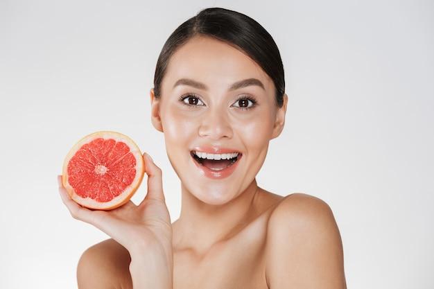 Di donna felice eccitata con pelle fresca sana tenendo succoso pompelmo rosso e guardando la fotocamera con un sorriso, isolato su bianco