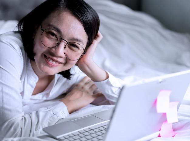 Di donna sorridente e portatile. lavora da casa concetto