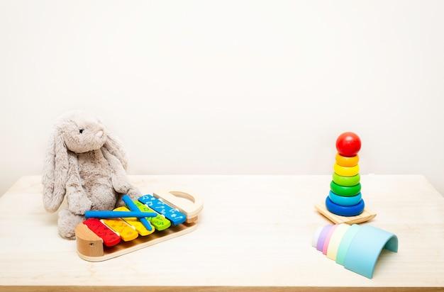 Di giocattoli colorati per bambini contro il muro giocattoli sul tavolo di legno con copyspace