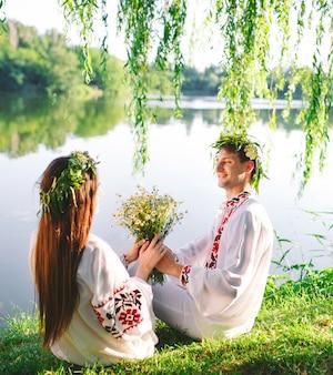Di mezza estate. giovani coppie amorose in costumi slavi sulla riva del lago. festa slava di ivan kupala.
