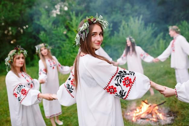 Di mezza estate. i giovani in abiti slavi ruotano attorno a un fuoco in piena estate. .
