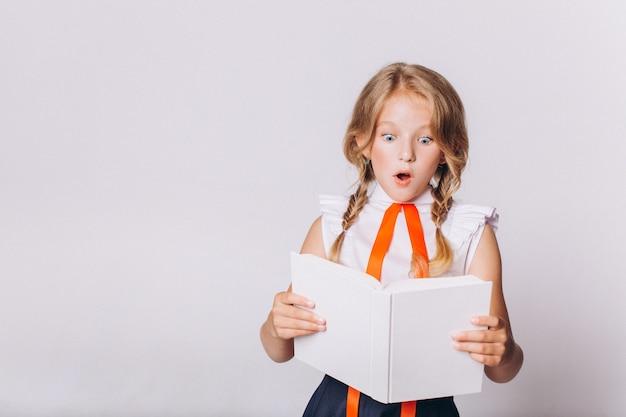 Di nuovo a scuola. carina adorabile ragazza bionda caucasica con il libro in uniforme scolastica su sfondo bianco