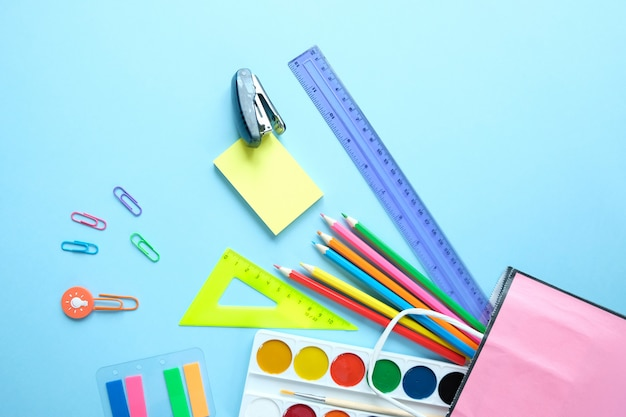 Di nuovo a scuola. i vari articoli di cancelleria su sfondo azzurro.