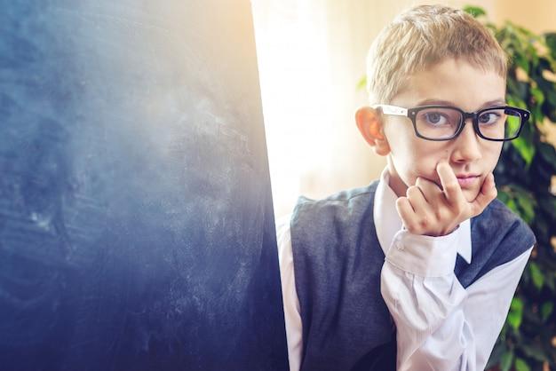 Di nuovo a scuola. il bambino intelligente risolve un compito in classe. il ragazzo sta scrivendo sulla lavagna