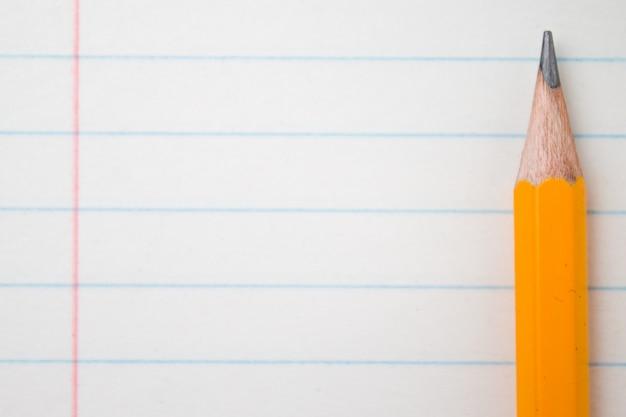 Di nuovo a scuola, il concetto di istruzione con le matite arancio si chiude su e libro della composizione sul bac