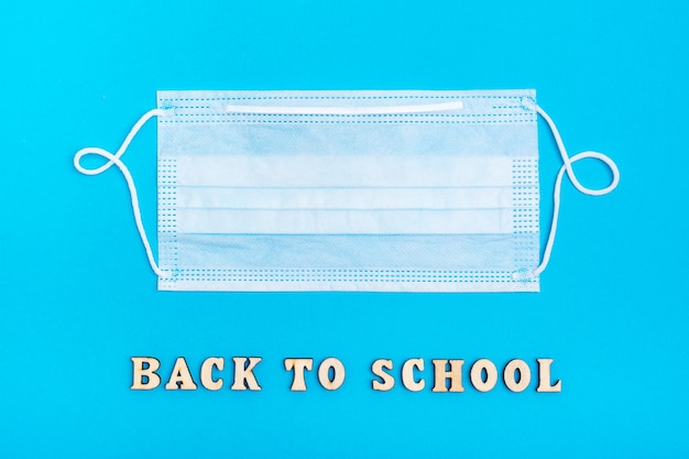 Di nuovo a scuola. l'iscrizione in lettere di legno e una mascherina medica protettiva su sfondo blu