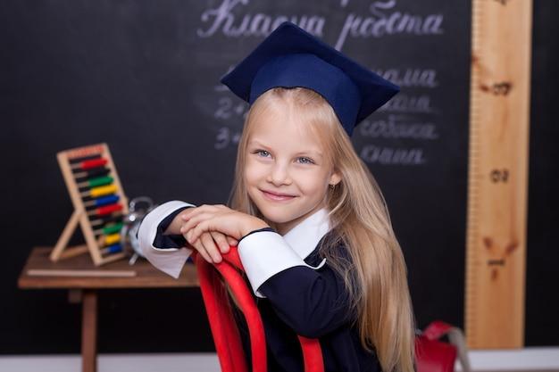 Di nuovo a scuola! la bambina allegra sta sedendosi sulla lezione.
