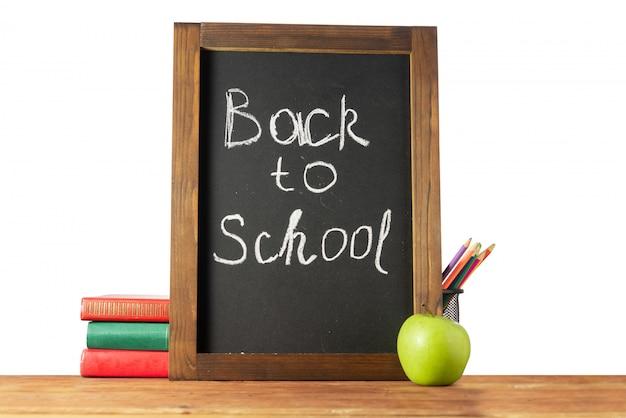 Di nuovo a scuola. lavagna, libri, mela di matite colorate