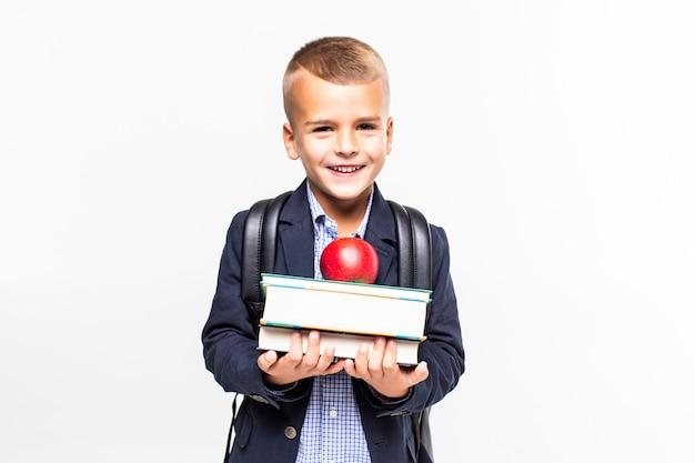 Di nuovo a scuola. libri, mela, scuola, ragazzo. il piccolo studente tiene i libri. piccolo bambino sorridente allegro contro la lavagna. concetto di scuola