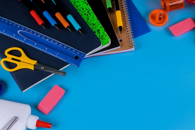 Di nuovo a scuola. materiale scolastico su sfondo blu