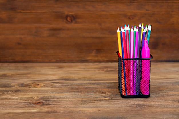 Di nuovo a scuola. matite colorate in un organizzatore su legno. copia spazio.