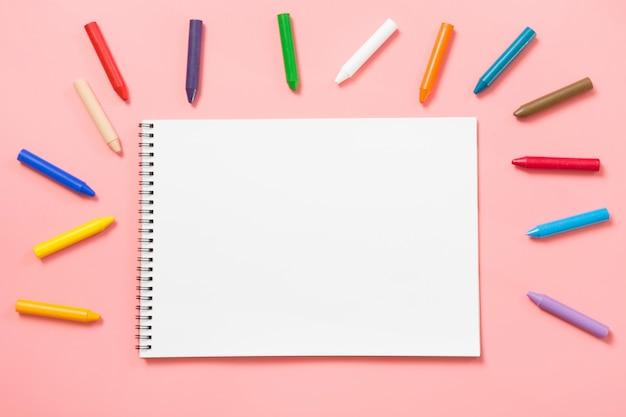 Di nuovo a scuola. pastelli a cera colorati e album su rosa pastello.