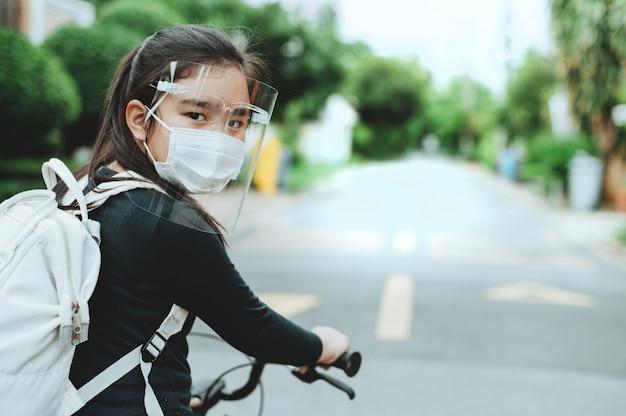 Di nuovo a scuola. ragazza asiatica del bambino che indossa la maschera con lo zaino in bicicletta una bicicletta e andare a scuola. pandemia di coronavirus. nuovo stile di vita normale. concetto di istruzione.