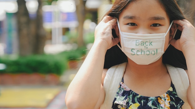 Di nuovo a scuola. ragazza asiatica del bambino che indossa la maschera con zaino andando a scuola. pandemia di coronavirus. nuovo stile di vita normale. concetto di istruzione.