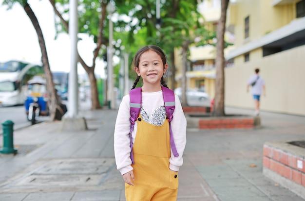 Di nuovo a scuola. ragazza asiatica felice del bambino con la cartella della spalla dello studente. piccola studentessa con uno zaino.