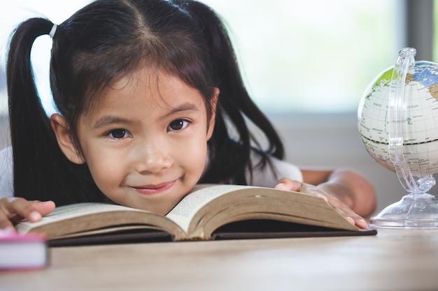 Di nuovo a scuola. ragazza asiatica sveglia del bambino con un libro che sorride nell'aula