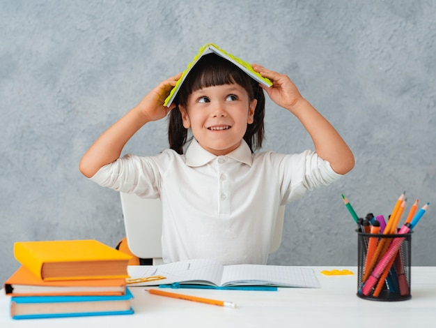 Di nuovo a scuola. scolara sveglia del bambino che si siede ad uno scrittorio in una stanza.