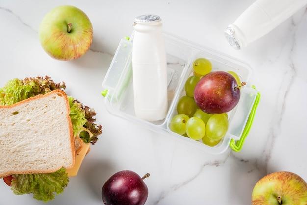 Di nuovo a scuola. un pranzo sano in una scatola è frutta fresca mele, prugne, uva, una bottiglia di yogurt e un panino con lattuga, pomodori, formaggio, carne. tavolo in marmo bianco. vista dall'alto