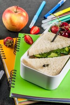Di nuovo a scuola. un sostanzioso pranzo scolastico sano in una scatola: panini con verdure e formaggio, bacche e frutta (mele) con quaderni, penne colorate su un tavolo nero.